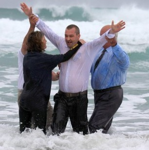This is the moment a vicar baptised a churchgoer in the sea - while wearing a dog collar and wetsuit