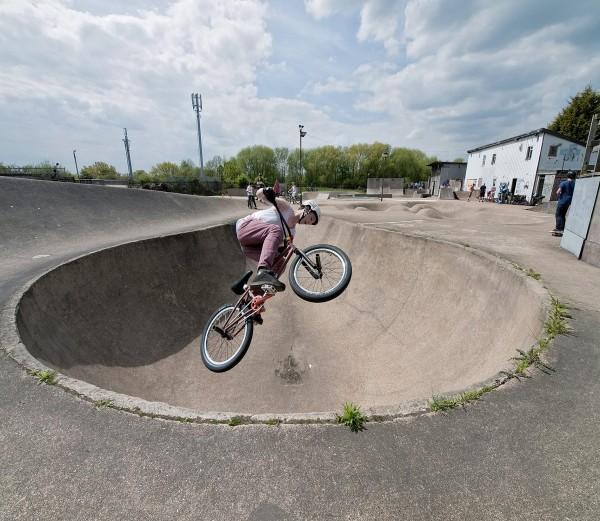 A BMX rider gets air in a concrete bowl at Rom skatepark