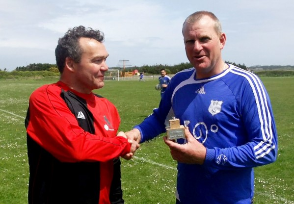 Alex Wade (left) from the Dynamo Choughs shakes hands with Martin Tomkinson from St Mary's FC as he holds the Lyonesse Cup the smallest trophy in football