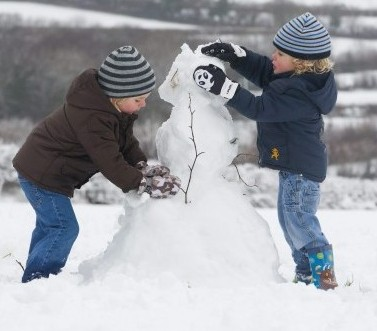 Brothers Jack Ribbons, 4, and Freddie Ribbons, 2, build a snowman together today as shoppers began panic buying to prepare for the weather