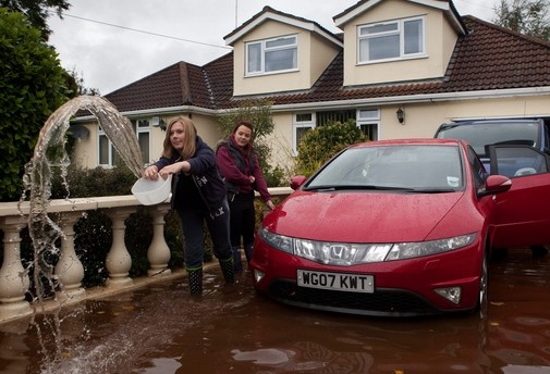 Bryony Coles, 17 watches her sister Courtney, 15, bail out water from the driveway of their home in Yatton, Somerset after heavy rain caused flash flooding