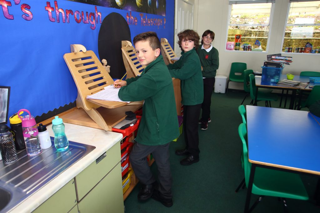 Oscar, Piper and Harvey are seen using the stand up desks at Kewstoke Primary School