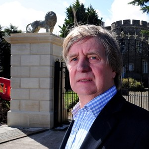 Edward Packer with the stone lions which he had built on a pair of pillars outside his home