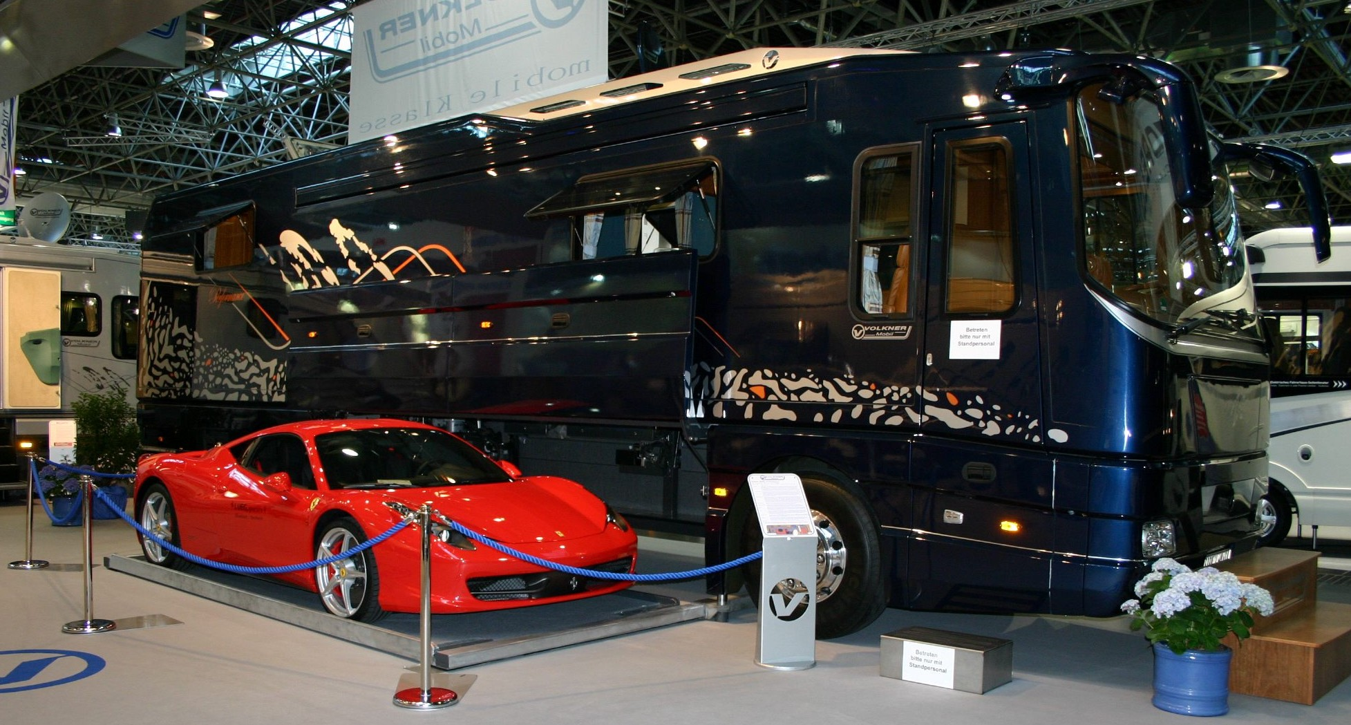 The sports car can be driven onto a cargo floor which then lifts and moves sideways into the motorhome