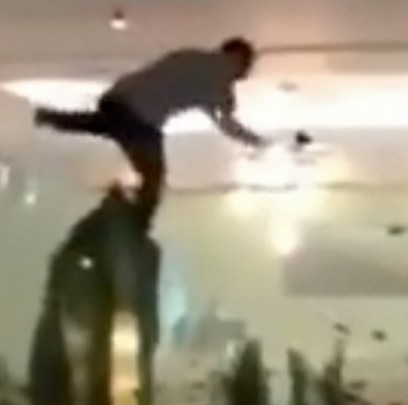 The drunk man is filmed clambering into the tropical fish tank at a hotel in Jersey