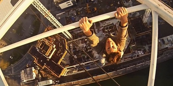 A daredevil hangs fom the top of a crane in Southampton docks