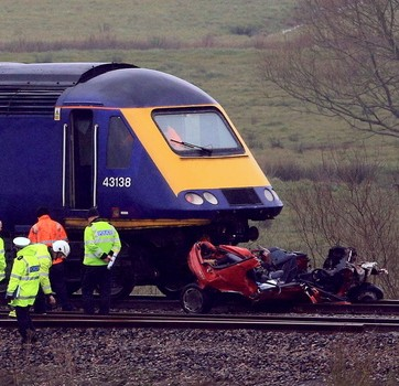 The wreckage of the car is seen crushed under the train