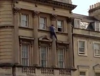 This daredevil window cleaner is captured on film balancing on a ledge without a safety harness on the third floor of a building in Bath