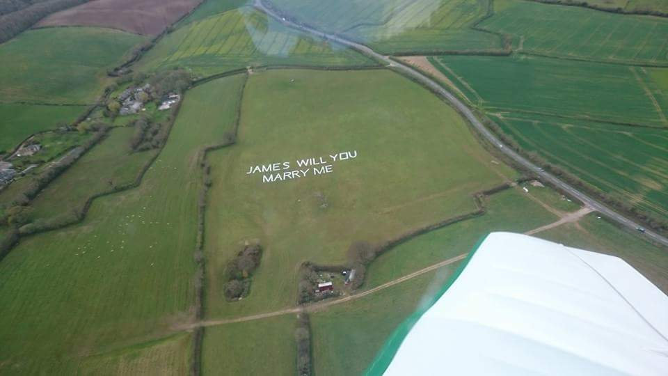 Speechless boyfriend flew over a huge proposal written out in giant letters.