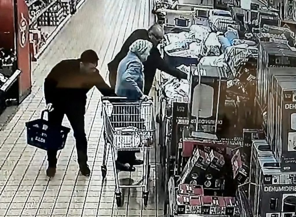 This is the shocking moment a thief snatches a purse from an elderly woman's bag as she shops in Aldi - while she is distracted by his accomplice.