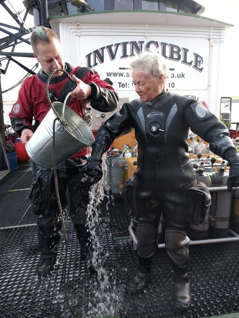 Pat having a bucket of water thrown on her after her 80th birthday dive.