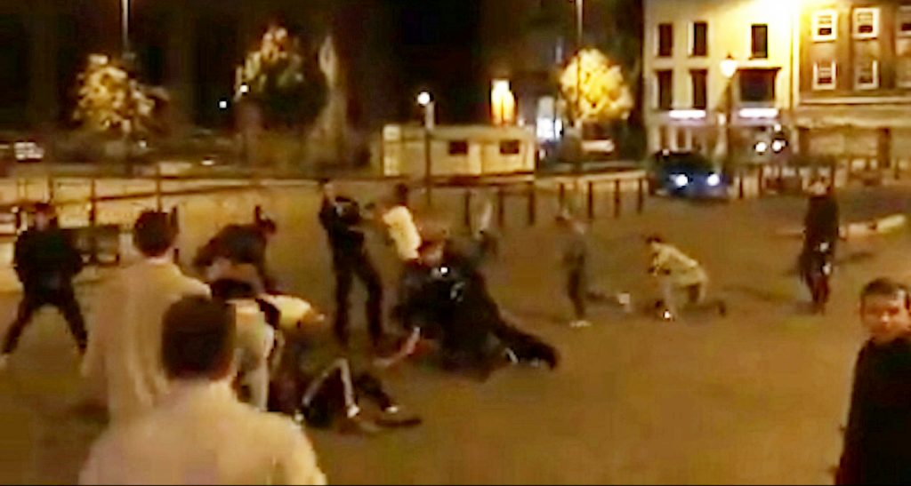 This is the shocking moment a police officer is punched to the ground during a mass brawl caused by someone having his MANBAG stolen.