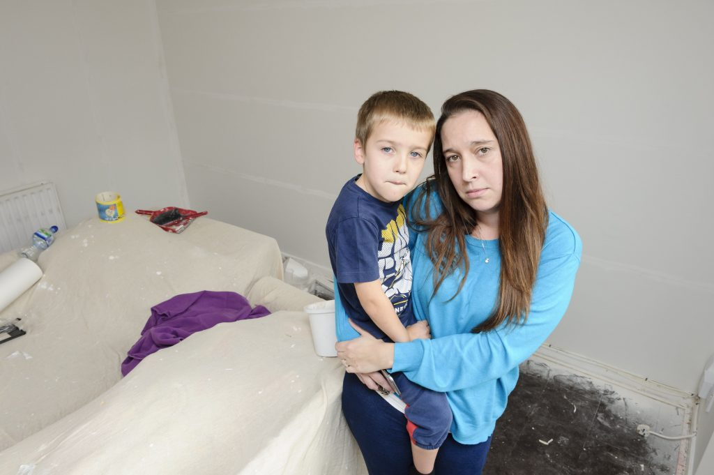 Rebecca Weston with son Lucas-James, 5, amidst the repairs to their house in Swanley, south east London.
